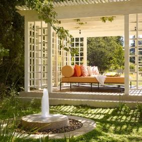 Садовый фонтанчик около беседки из дерева