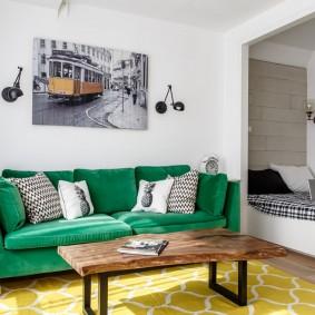 Зеленый диван в небольшой комнате