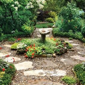 Каменистая дорожка к клумбе с фонтаном