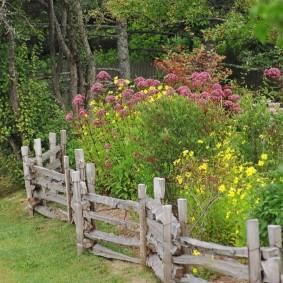 Деревянный заборчик в саду сельского стиля