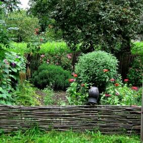 Старый плетень в саду деревенского стиля