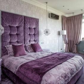 Фиолетовая обивка стены над изголовьем кровати