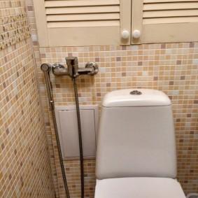 Декор стены туалета мелкой керамической плиткой