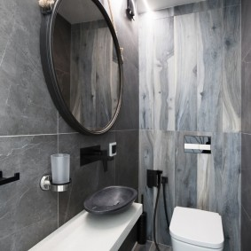 Круглое зеркало на раковиной в туалете