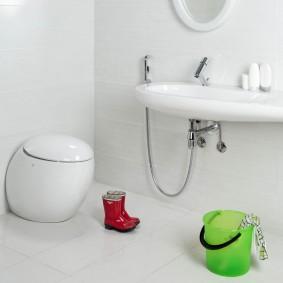 Зеленое ведро около раковины в туалете