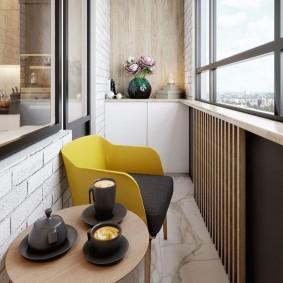 Желтое кресло в интерьере балкона