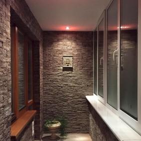 Серый камень на стене застекленной лоджии