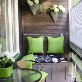 Зеленые подушки над скамейкой с ящиками