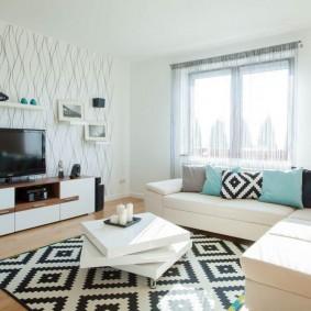 Белый диван перед окном в однокомнатной квартире