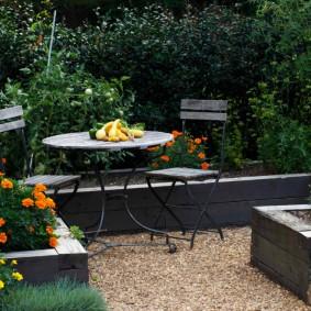 Оранжевые бархатцы на высокой клумбе в саду
