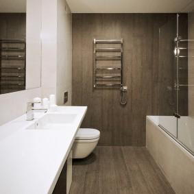 Хромированный полотенцесушитель на коричневой стене
