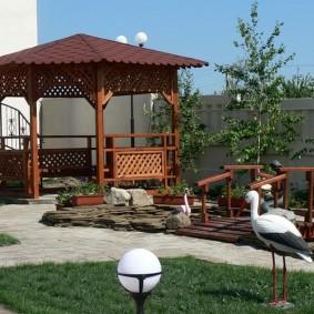 Декор садового участка с деревянной беседкой