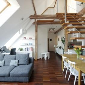 Серый диван под окном мансардного типа