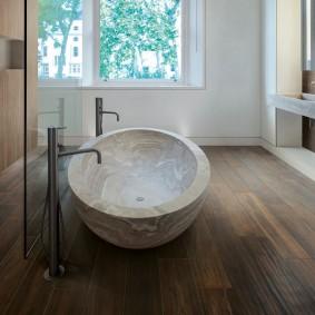 Белая чаша ванны на фоне ламинированного пола