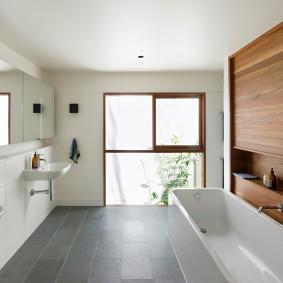 Длинная ванна под стеной с влагостойким ламинатом