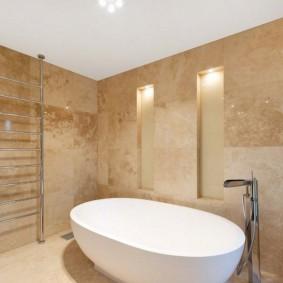 Белая чаша ванны на фоне светло-коричневых стен