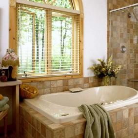 Встроенная пластиковая ванна перед деревянным окно