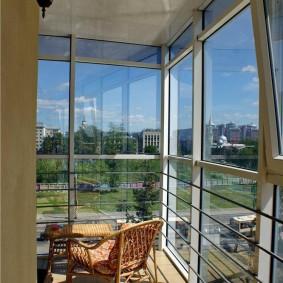 Плетенное кресло на балконе с панорамным окном