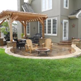 Патио с деревянной перголой у двухэтажного дома