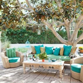 Мягкая мебель в тени высокого дерева