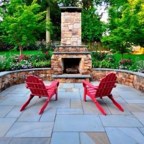 Красные кресла перед садовым камином