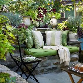 Каменный диванчик с мягкими подушками