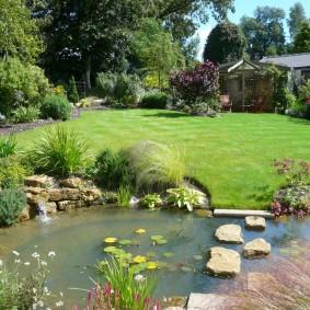 Тропинка из камней через водоем в саду