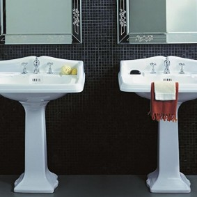 Белая сантехника в ванной с черной плиткой