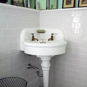 Фарфоровый умывальник в углу ванной комнаты