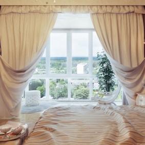 Белые шторы с подхватами на окне спальни