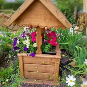 Миниатюрный колодец на садовой клумбе