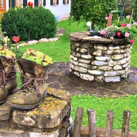 цветы в старых ботинках на столбе забора