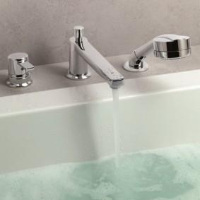 Струя чистой воды из смесителя в ванной