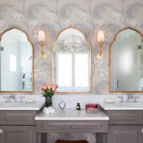 Зеркала в позолоченных рамках на умывальниками в ванной