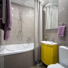 Желтая тумба в ванной с унитазом