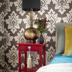 Столик красного цвета у спинки кровати