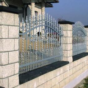 Кованный забор на бетонных столбах с каменной облицовкой