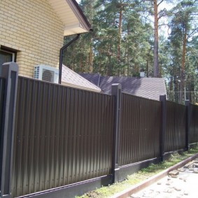 Высокая ограда на бетонных столбах