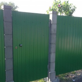 Зеленый профлист на столбах из бетона