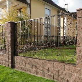 Ажурная ковка на заборе с бетонными столбами