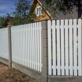Белый штакетник в комбинации с бетонными столбами