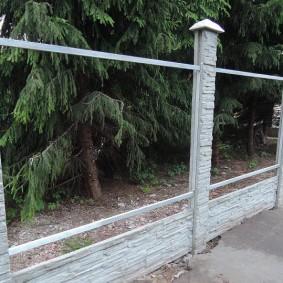 Металлические прожилины между бетонными столбами