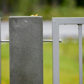 Крепление металлической секции забора к бетонному столбу