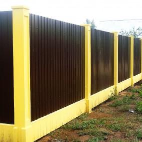 Желтые бетонные столбы в комбинации с темным профлистом