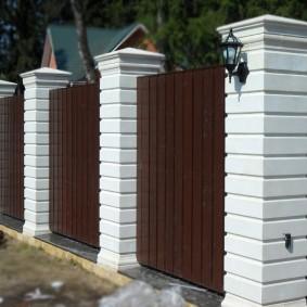Садовая ограда с белыми столбами