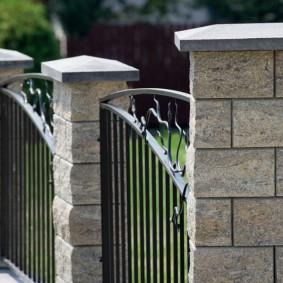 Каменные колпаки на бетонных столбах ограды