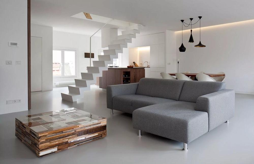 Серый угловой диван в двухуровневой квартире-студии