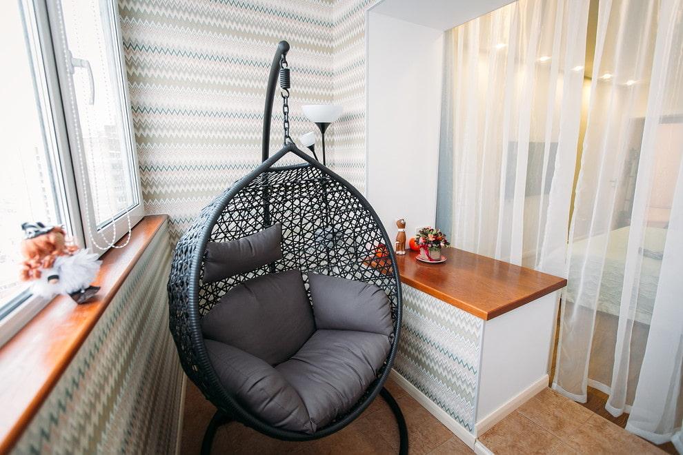 Подвесное кресло из ротанга в интерьере балкона