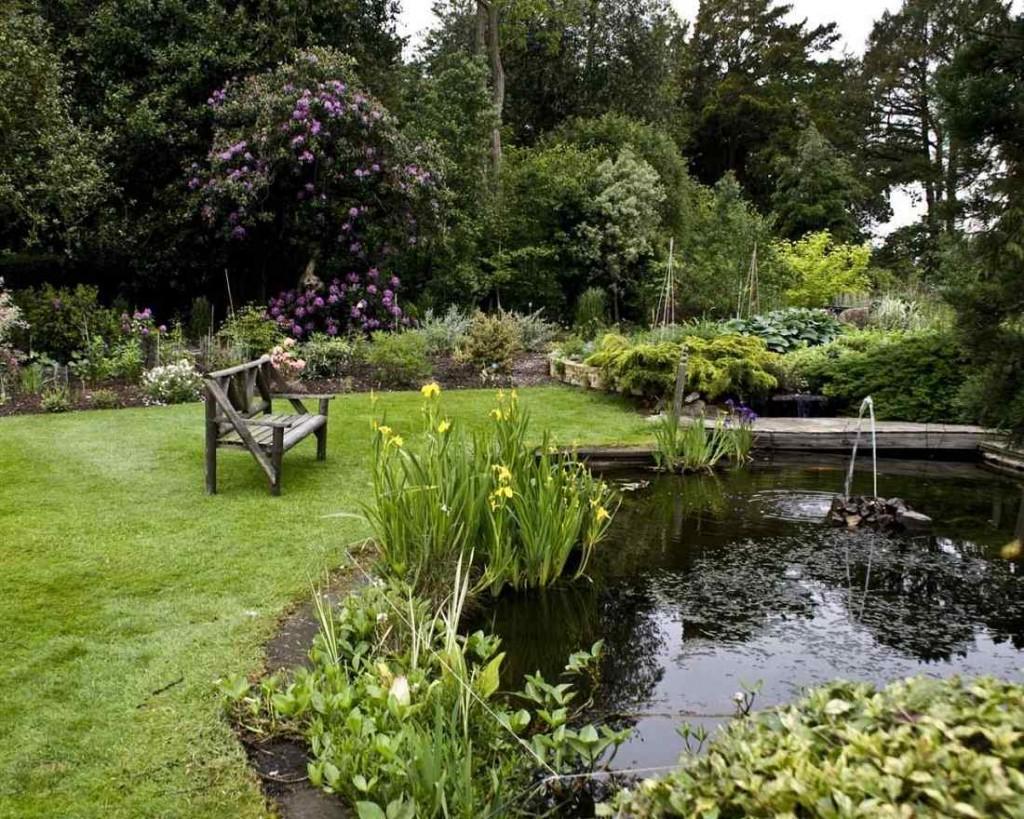 Скамейка на газоне садового участка в английском стиле