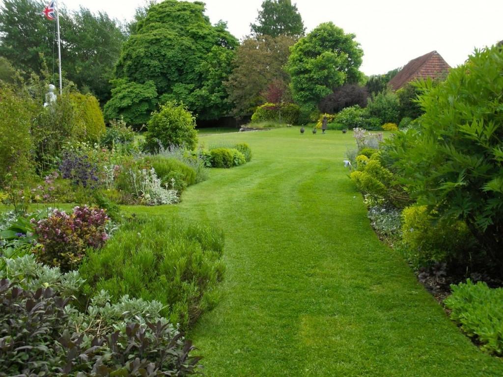 Зеленая лужайка в саду английского стиля